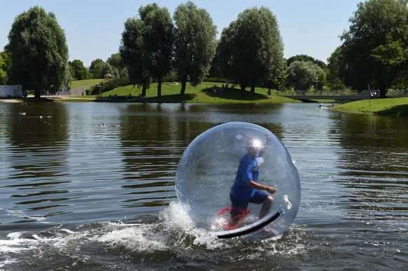 epa04787872 Walking on Water - Todor uses a so-called 'Waterball' to walk on the waters of the pond of the Olympic Park in Munich, Germany, 07 June 2015. Although it appears to be fun to walk on the water surface inside a giant inflatable ball it would be more refreshing to enjoy the water without the ball at temperatures of up to 28 degrees Celsius this weekend.  EPA/FELIX HOERHAGER
