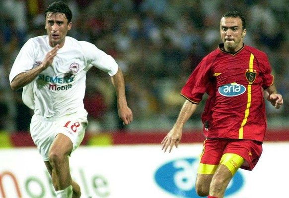 Antzas of Olympiakos Piraeus, left, and Galatasaray's Arif Erdem challenge for the ball at Ataturk Olympic stadium in Istanbul, Turkey, Wednesday July 31, 2002, during  a friendly soccer game between Galatasaray and Olypiakos Piraeus of Greece. (AP Photo/Str)