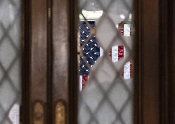 Broken glass from last week's confrontation with a pro-Trump mob is seen in the door to the House chamber at the Capitol in Washington, Tuesday, Jan. 12, 2021. House Speaker Nancy Pelosi, D-Calif., is calling for swift congressional action to rein in President Donald Trump after inciting last week's deadly assault on the U.S. Capitol. (AP Photo/J. Scott Applewhite)