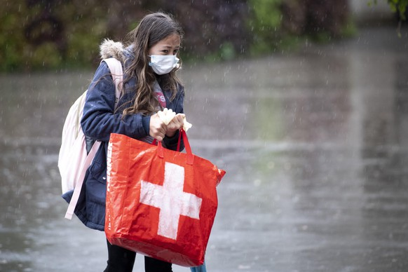 A pupil wearing a protective mask arrives at a primary school Etablissement Primaire de l'ecole vaudoise, in Morges, Switzerland, Monday, 11 May 2020. Classroom teaching at primary and lower secondary schools will again be permitted. Shops, markets, museums, libraries and restaurants reopen under strict compliance with precautionary measures as a precaution against the spread of the coronavirus COVID-19. (Laurent Gillieron/Keystone via AP)