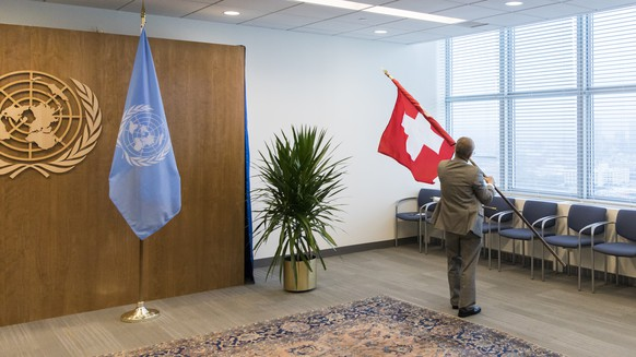 A staff member mounts a Swiss flag next to the UN flag before a bilateral meeting of Swiss Federal President Alain Berset and United Nations Secretary-General Antonio Guterres, at the 73rd session of the General Assembly of the United Nations at United Nations Headquarters in New York, New York, USA, September 26, 2018. (KEYSTONE/Peter Klaunzer)