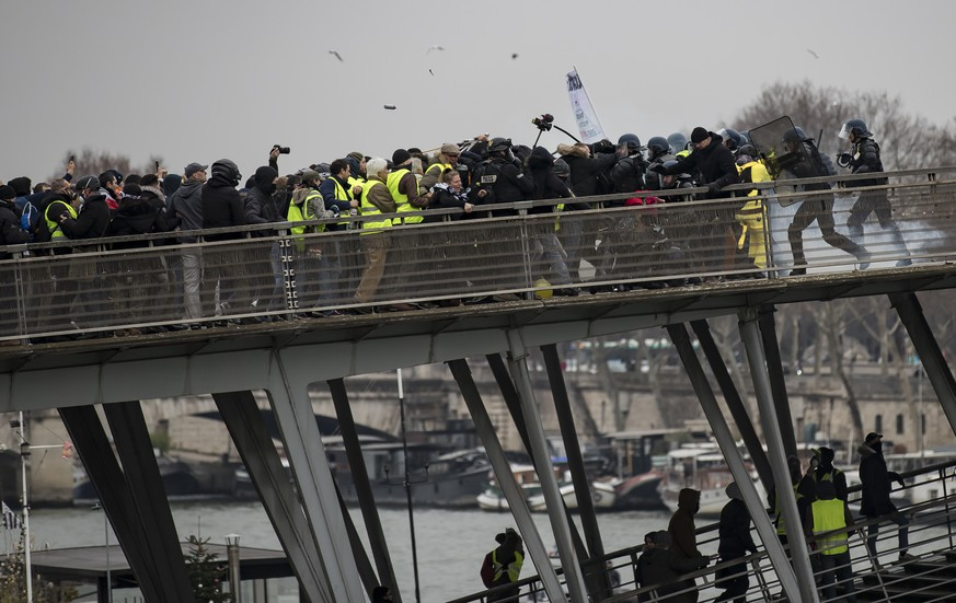 epa07264060 Protesters try to cross a bridge over the Seine river during a 'Yellow Vests' protest in Paris, France, 05 January 2019. The so-called 'gilets jaunes' (yellow vests) is a grassroots protest movement with supporters from a wide span of the political spectrum, that originally started with protest across the nation in late 2018 against high fuel prices. The movement in the meantime also protests the French government's tax reforms, the increasing costs of living and some even call for the resignation of French President Emmanuel Macron.  EPA/IAN LANGSDON