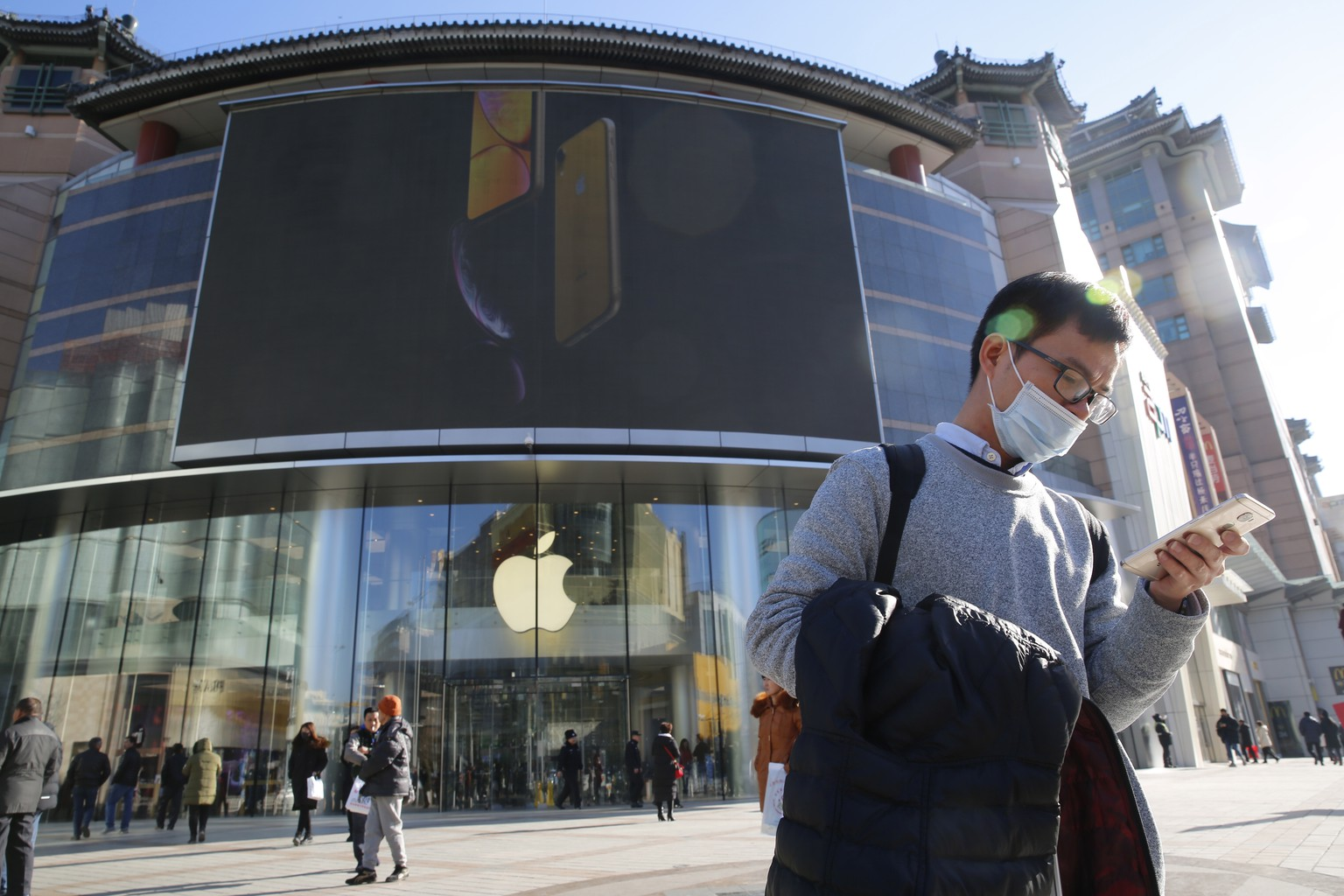 epa07259019 (FILE) - A Chinese man uses his mobile phone outside an Apple store while an iPhone XR picture is displayed on a large screen in Beijing, China, 12 December 2018 (reissued 03 January 2019). Apple annouced its predicted revenue for three months to 29 December 2018 this week, noting nearly a five percent decline on the same time the previous year.  EPA/WU HONG