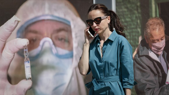epa09370807 A woman walks in front of a banner showing a medical worker, at a street in Moscow, Russia, 27 July 2021. Russia is facing a third wave of the coronavirus disease (COVID-19).  EPA/YURI KOCHETKOV