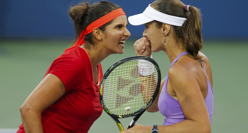 Sania Mirza of India (L) confers with playing partner Martina Hingis of Switzerland during their women's doubles semifinals match against Sara Errani and Flavia Pennetta, both of Italy, at the U.S. Open Championships tennis tournament in New York, September 9, 2015. REUTERS/Eduardo Munoz