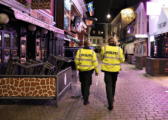 epa08683722 Police patrol the amusement street Jomfru Ane Gade after 22.00 o'clock in Aalborg, Denmark, 19 September 2020 (issued 20 September 2020). The government's new restrictions have come into force on 19 September and the restrictions mean, among other things, that restaurants, cafes and pubs must close at 10pm. At the same time, North Jutland Police issued a restraining order in Jomfru Ane Gade. This means that you must walk through the party street, but you must not stop.  EPA/Henning Bagger  DENMARK OUT