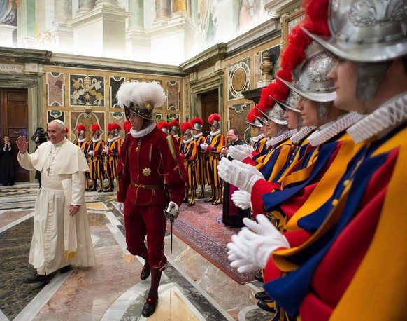 In this photo taken Monday, May 5, 2014, and provided by the Vatican newspaper L'Osservatore Romano, Pope Francis, flanked by Swiss Guards Commander Daniel Rudolf Anrig, greets new Swiss Guards the day before their swearing-in ceremony, as he arrives to meet them in the Clementine hall at the Vatican.  (AP Photo/L'Osservatore Romano)