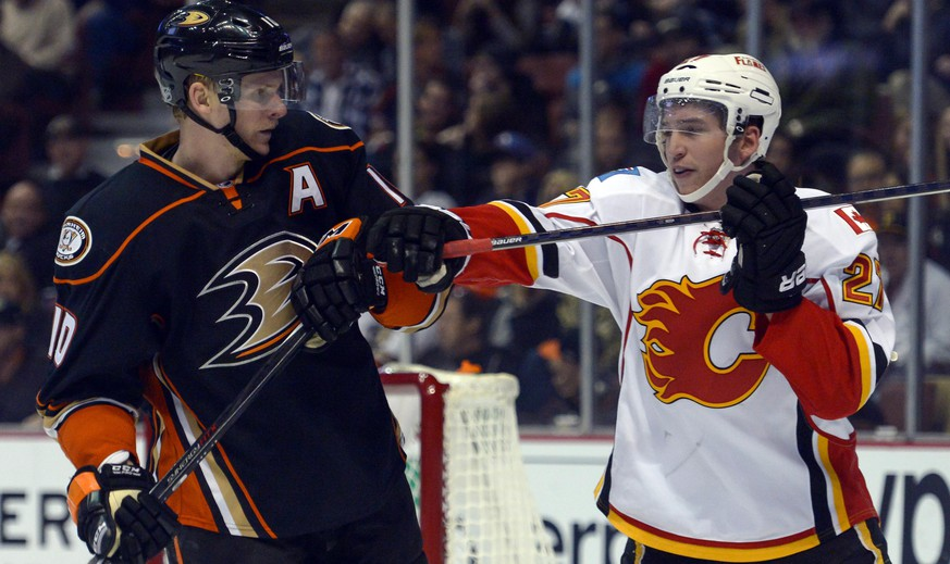 Nov 25, 2014; Anaheim, CA, USA; Calgary Flames left wing Sven Baertschi (27) takes a shot at Anaheim Ducks right wing Corey Perry (10) during the third period at Honda Center. Mandatory Credit: Robert Hanashiro-USA TODAY Sports