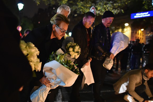 PARIS, FRANCE - NOVEMBER 14:  Bono and band members from the band U2 place flowers on the pavement near the scene of yesterday's Bataclan Theatre terrorist attack on November 14, 2015 in Paris, France. At least 120 people have been killed and over 200 injured, 80 of which seriously, following a series of terrorist attacks in the French capital.  (Photo by Jeff J Mitchell/Getty Images)