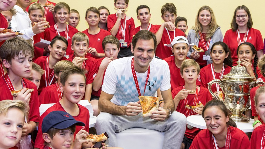 epa06297283 Switzerland's Roger Federer (C) eats pizza with ball kids after defeating Argentina's Juan Martin del Potro in their final match of the Swiss Indoors tennis tournament at the St. Jakobshalle in Basel, Switzerland, 29 October 2017.  EPA/ALEXANDRA WEY