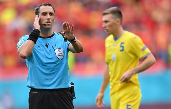 epa09279780 Argentinian referee Fernando Andres Rapallini checks with the VAR during the UEFA EURO 2020 group C preliminary round soccer match between Ukraine and North Macedonia in Bucharest, Romania, 17 June 2021.  EPA/Stuart Franklin / POOL (RESTRICTIONS: For editorial news reporting purposes only. Images must appear as still images and must not emulate match action video footage. Photographs published in online publications shall have an interval of at least 20 seconds between the posting.)