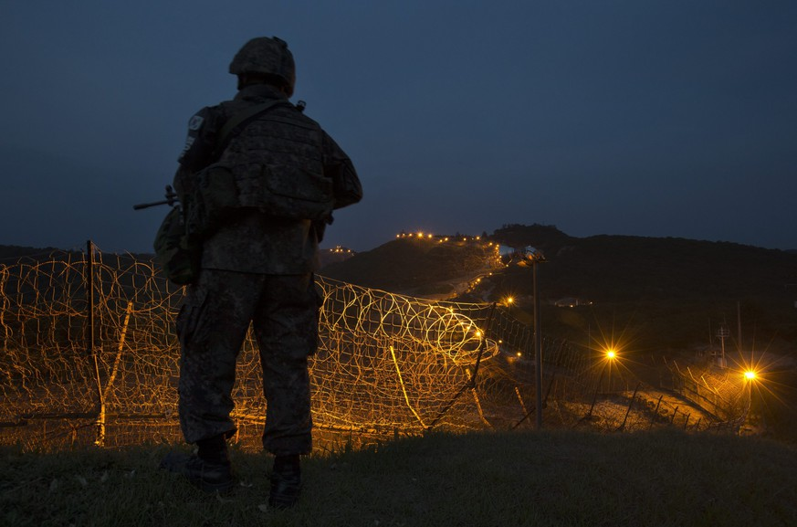 epa04816075 A soldier of South Korean Army's 6th Division is on night guard duty near a barbed-wire fence inside the Demilitarized Zone (DMZ) separating the two Koreas, at the central section of the inter-Korean border in Cheorwon, Gangwon Province, South Korea, 23 June 2015, two days ahead of the 65th anniversary of the start of the 1950-53 Korean War. The four-kilometer-wide DMZ, established at the end of the three-year conflict, serves as a buffer zone between the two Koreas.  EPA/YONHAP SOUTH KOREA OUT