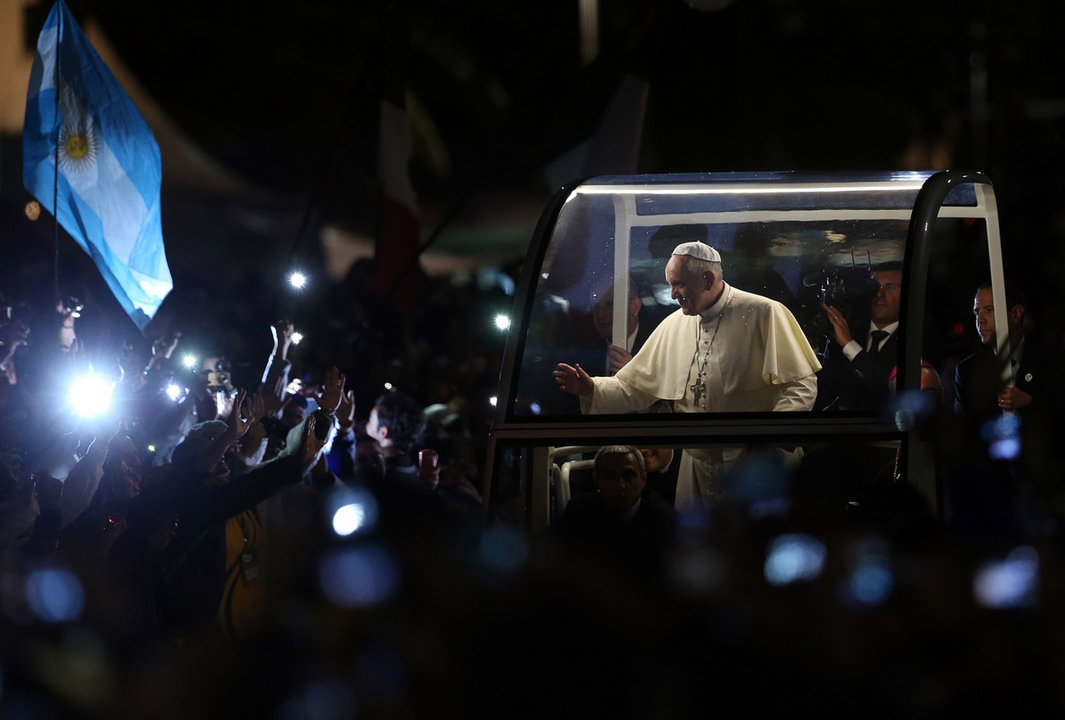 Pope Francis waves as arrives for a World Youth Day celebration on the Copacabana beachfront in Rio de Janeiro, Brazil, Thursday, July 25, 2013. Francis traveled in his open-sided car through a huge crowd in the pouring rain to a welcoming ceremony on Copacabana beach. It was his first official event with the hundreds of thousands of young people who have flocked to Rio for World Youth Day. Vatican officials estimated the crowd at 1 million. (AP Photo/Andre Penner)