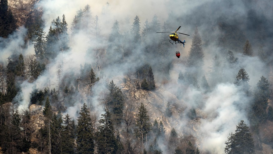 A fire fighting helicopter discharges water over the forest fires near Mesocco in Southern Switzerland, Wednesday, December 28, 2016. (KEYSTONE/Ti-Press/Gabriele Putzu)