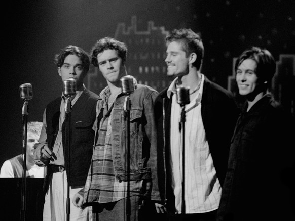 NETHERLANDS - 1st JANUARY: English boy band Take That perform live on stage in the Netherlands in 1993. Left to Right: Gary Barlow, Robbie Williams, Howard Donald,  Jason Orange and Mark Owen. (Photo by Michel Linssen/Redferns)