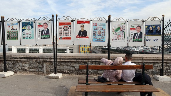 epaselect epa06344167 An Algerian couple sits near poster for the next local elections in Algiers, Algeria, 22 November 2017. Voting for the local elections is scheduled for 23 November 2017. Nearly 23 million Algerian voters are called to the polls to choose their representatives.  EPA/MOHAMED MESSARA