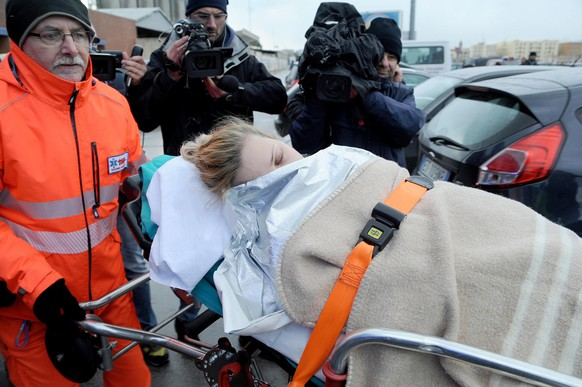 epa04542048 An injured passenger of the stricken Greek ferry 'Norman Atlantic' is stretchered off the freight ship 'Spirit of Piraeus'  that brought her to the port city of Bari, Italy, 29 December 2014.  Rescue services at the harbour were preparing for an extended session as more rescued individuals were expected. Hospitals in the city were also on standby, media reports say there are no seriously injured passengers on board the burning ferry.