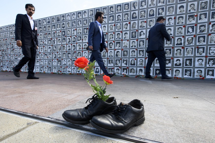 epa06207081 People pass by a wall of photos of victims of the 1988 Massacre of political prisoners in Iran during an exhibition at the Palais des Nations in front of the United Nations (UN) European Headquarters in Geneva, Switzerland, 15 September 2017. The shoes with flowers represent the victims of the mass execution. In the summer of 1988, some 30,000 Iranian political prisoners were massacred in a matter of a few months on the basis of a fatwa issued by Ruhollah Khomeini, the founder of the Islamic Republic. Human rights organizations and jurists are demanding the UN to conduct an independent international investigation of the 1988 massacre.  EPA/MARTIAL TREZZINI