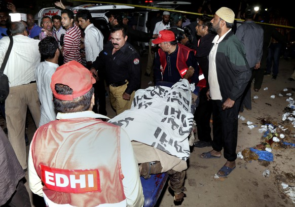 Pakistani rescue workers remove a dead body from the site of bomb blast in a park in Lahore, Pakistan, Sunday, March, 27, 2016. A bomb blast in a park in the eastern Pakistani city of Lahore has killed tens of people and wounded scores, a health official said. (AP Photo/K.M. Chuadary)