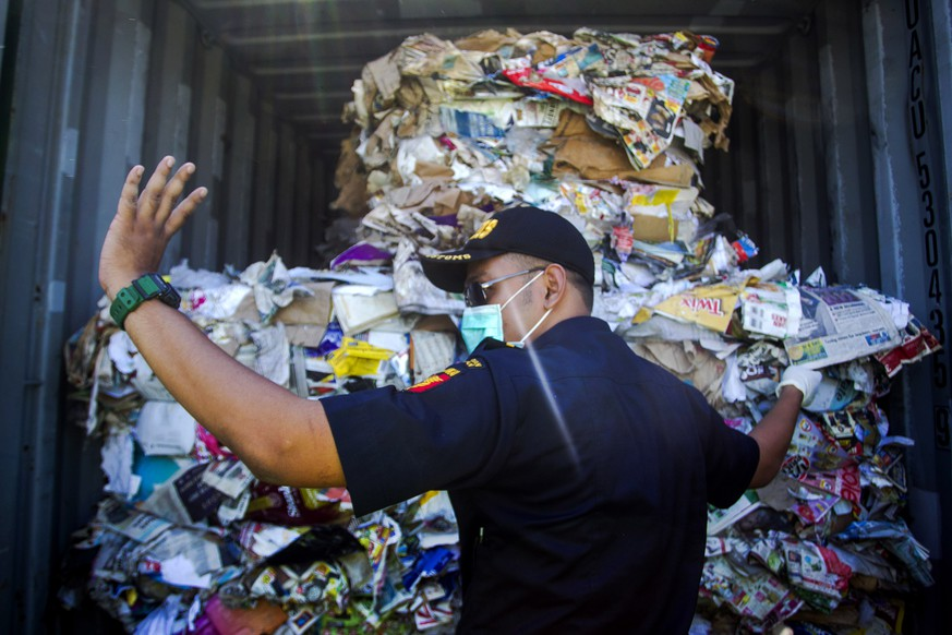 epa07704715 An Indonesian customs official inspects containers loaded with a combination of garbage, plastic waste and hazardous materials from Australia at Tanjung Perak port in Surabaya, East Java, Indonesia, 09 July 2019. Indonesia's authorities will ship 210 tons of contaminated waste back to Australia.  EPA/FULLY HANDOKO