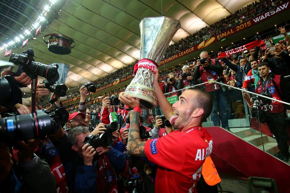 WARSAW, POLAND - MAY 27: Aleix Vidal of Sevilla lifts the trophy as he celebrates victory after the UEFA Europa League Final match between FC Dnipro Dnipropetrovsk and FC Sevilla on May 27, 2015 in Warsaw, Poland.  (Photo by Martin Rose/Getty Images)
