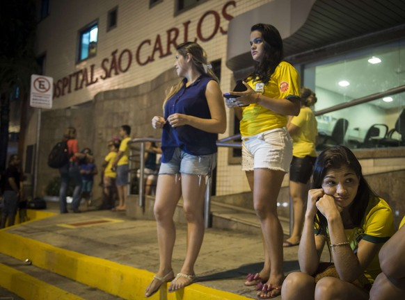 Brazilian football fans stand outside the Sao Carlos hospital  waiting for news on the condition of Neymar  in Fortaleza on July 5, 2014. Brazil star Neymar was ruled out of the World Cup after that with a back injury, team doctor Rodrigo Lasmar said. Lasmar told reporters Neymar suffered a fracture in the third verterbra of his back during Brazil's bruising 2-1 quarter-final victory over Colombia.. AFP PHOTO / ODD ANDERSEN