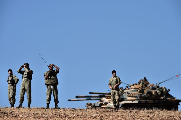 Officers stand in front of Turkish tanks as they line up on a hill outside the village of Mursitpinar next to the Syrian town of Ain al-Arab, known as Kobane by the Kurds, on the Turkish-Syrian border  on October 6, 2014. Turkish security forces on Monday used tear gas to push dozens of reporters and Kurdish civilians away from the border zone close to intense fighting for the besieged Syrian town of Kobane. AFP PHOTO / ARIS MESSINIS