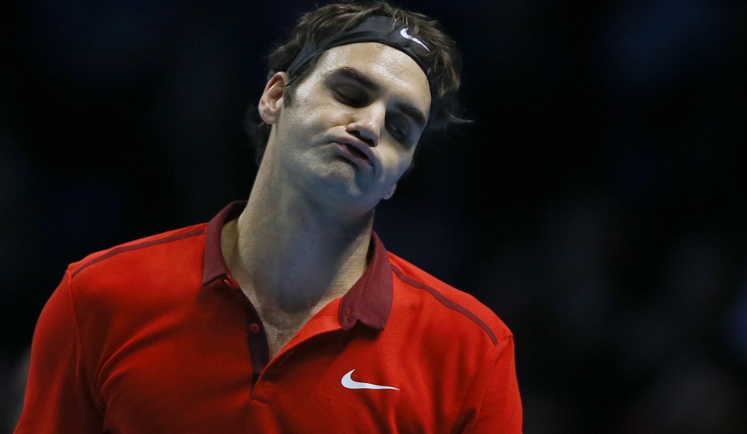 In this photo taken Saturday, Nov. 15, 2014, Switzerland's Roger Federer sighs after losing a point during his singles ATP World Tour Finals semifinal tennis match against Switzerland's Stan Wawrinka at the O2 Arena in London. Roger Federer has withdrawn from the final he was due to play against Serbia's Novak Djokovic on Sunday because of a back injury. (AP Photo/Kirsty Wigglesworth)