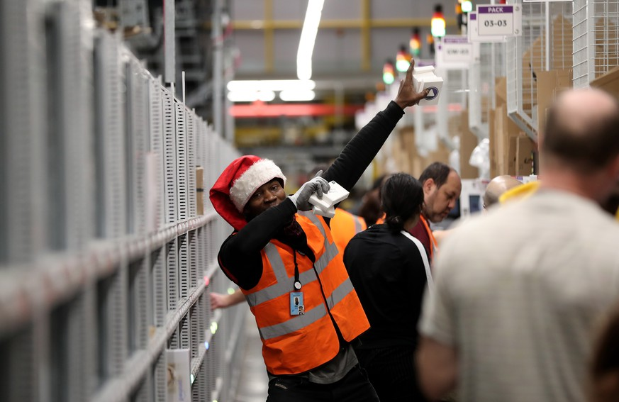 epa08077440 An Amazon employee poses at the Amazon logistic and distribution center in Moenchengladbach, Germany, 17 December 2019. According to the company, Amazon has invested around 105 million euros in the most modern logistics centre in Europe. A technology developed by Amazon itself ensures that the robots drive the shelves to the warehouse workers.  EPA/FRIEDEMANN VOGEL