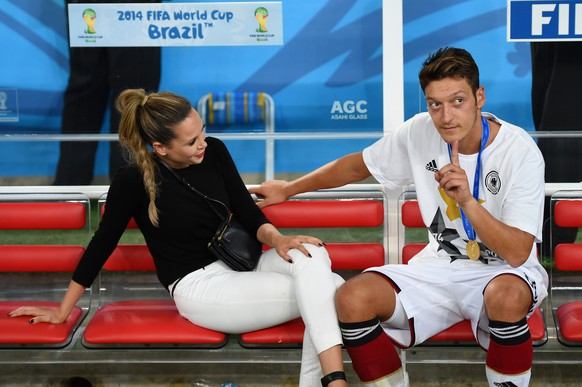 RIO DE JANEIRO, BRAZIL - JULY 13:  Mesut Oezil of Germany speaks to Mandy Capristo on the bench after defeating Argentina 1-0 in extra time during the 2014 FIFA World Cup Brazil Final match between Germany and Argentina at Maracana on July 13, 2014 in Rio de Janeiro, Brazil.  (Photo by Matthias Hangst/Getty Images)