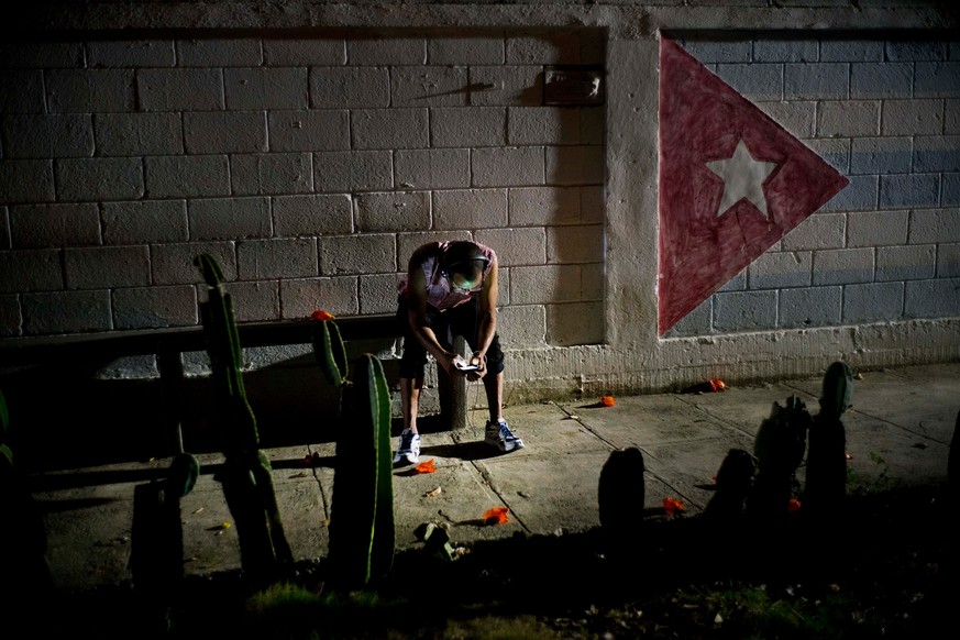 Lazaro Rodriguez, 42, connects his cellphone at a public internet hot spot at night in Havana, Cuba on Saturday, April 14, 2018. Lazaro, who studied baking and is currently working in maintenance, said he's seen very positive changes in the economy in recent years, and would like to see development continue.