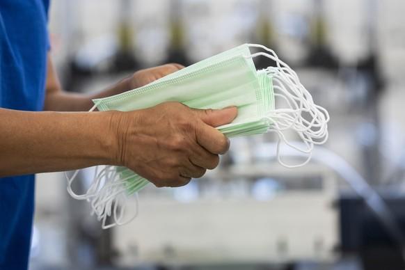 Mitarbeiter verarbeiten die Schutzmasken, die chirurgischen OP-Masken Typ II R, bei dem Verbandsstoffhersteller Wernli AG in Rothrist, aufgenommen am Dienstag, 28. April 2020. (KEYSTONE/Ennio Leanza)