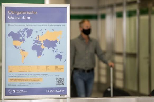 Ein Plakat weist auf die Obligatorische Quarantaene bei der Einreise aus bestimmten Laendern, bei der Ankunft am Flughafen Zuerich, aufgenommen am Dienstag, 21. Juli 2020. (KEYSTONE/Alexandra Wey)