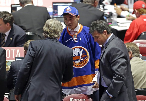 Andong Song, center, of China, shakes hand withe team executives after being chosen 172nd overall by the New York Islanders during the sixth round of the NHL hockey draft, Saturday, June 27, 2015, in Sunrise, Fla. (AP Photo/Alan Diaz)