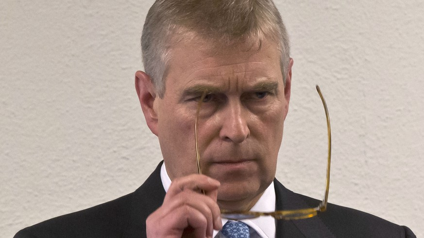 "FILE - In this file photo dated Thursday, Jan. 22, 2015, Britain's Prince Andrew, puts on his glasses prior to his speech to business leaders during a reception at the sideline of the World Economic Forum in Davos. Britain's Prince Andrew said Wednesday Nov. 20, 2019, that he is stepping back from public duties with the queen's permission, saying that recent disclosures regarding his association with the late convicted sex offender Jeffrey Epstein have become a ""major distraction"" to the royal family's work. (AP Photo/Michel Euler, FILE) Prince Andrew"