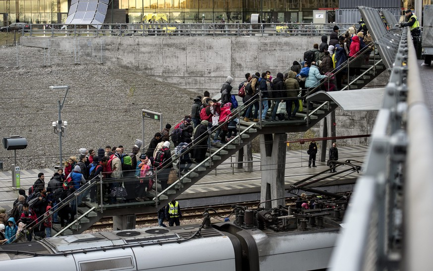 epa05034548 A photograph made available on 20 November 2015 shows police organizing the line of refugees on the stairway leading up from the trains arriving from Denmark, at the Hyllie train station outside Malmo, Sweden, 19 November 2015. Some 600 refugees arrived to Malmo late 19 November while the Swedish Migration Agency said in a press statement that they no longer can guarantee accommodation for all asylum seekers.  EPA/JOHAN NILSSON SWEDEN OUT