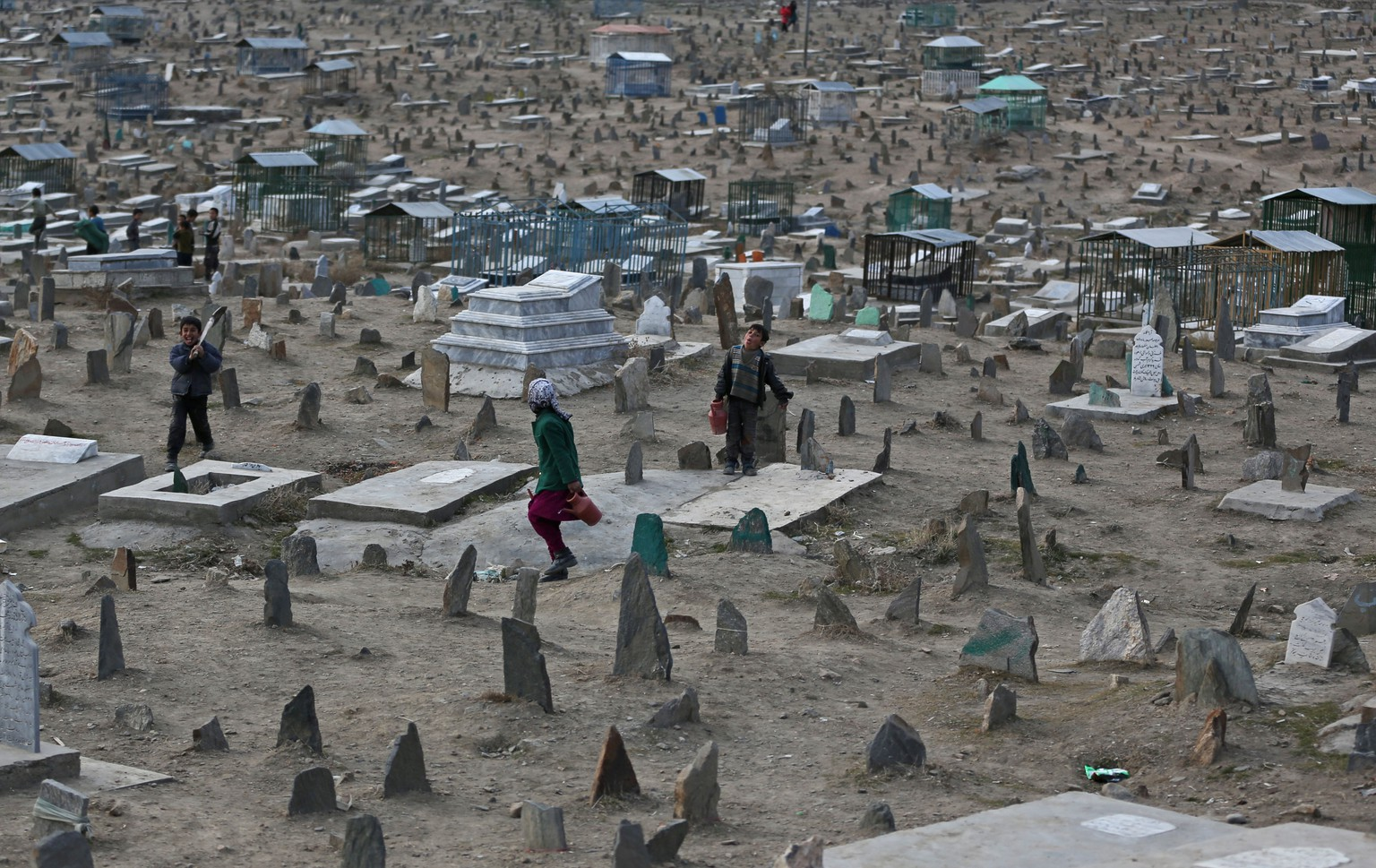 Afghan children wait for customers to sell water in Kart-e Sakhi cemetery in Kabul, Afghanistan, Wednesday, Jan. 29, 2014. Children sell water in cemeteries for visitors to pour it on their relatives' graveyards. (AP Photo/Massoud Hossaini)