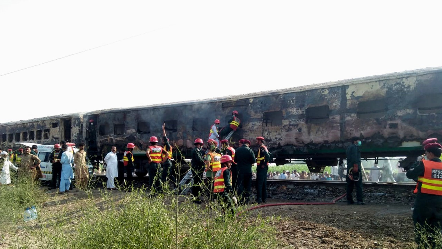 epa07961658 Rescue workers shift the bodies of the victims after a fire engulfed a passenger train near Rahim Yar Khan, Pakistan, 31 October 2019. Dozens were killed and more than 40 others injured after a fire erupted from a gas canister blast engulfed a train completely destroying at least three coaches.  EPA/STRINGER