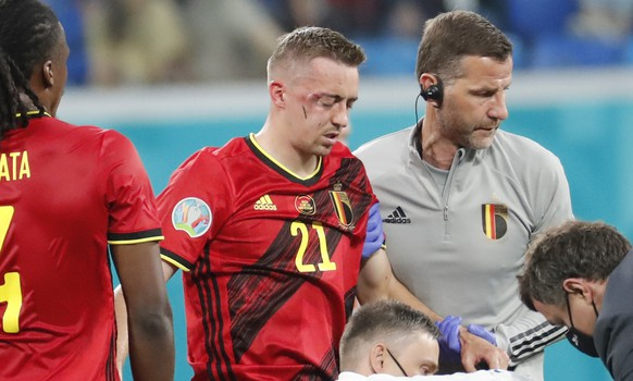 Belgium's Timothy Castagne, second from right, looks at Russia's Daler Kuzyayev helped by medical personnel during the Euro 2020 soccer championship group B match between Belgium and Russia at the Saint Petersburg stadium in St. Petersburg, Russia, Saturday, June 12, 2021. (Anatoly Maltsev/Pool via AP)
