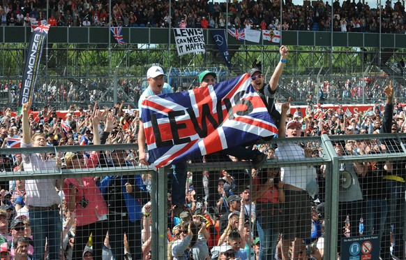 Motor racing fans celebrate after Britain's Lewis Hamilton of Mercedes won the British Formula One Grand Prix at Silverstone, England, on Sunday, July 6, 2014. Finland's Valtteri Bottas of Williams finished second with Australia's Daniel Ricciardo of Red Bull in third place. (AP Photo/Rui Vieira)