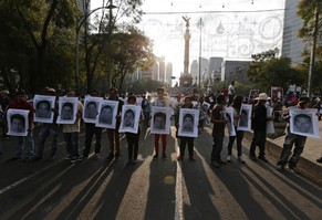 Demonstrators carry photographs of the 43 missing trainee teachers, during a march in front of the Angel of Independence statue in Mexico City December 6, 2014. The remains of one of 43 trainee teachers abducted in southwestern Mexico 10 weeks ago and believed to have been massacred by drug gang henchmen have been identified from tests, a source close to the investigation said on Saturday.    REUTERS/Tomas Bravo (MEXICO - Tags: CIVIL UNREST CRIME LAW POLITICS TPX IMAGES OF THE DAY)