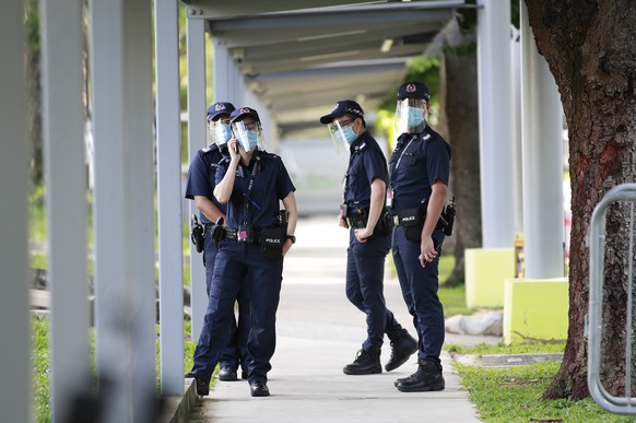 epa08517095 Police officers wearing protective face shields patrol a walkway before the arrival of candidates at a nomination centre in Singapore, 30 June 2020. Candidates standing for the 18th general elections file their nomination papers on nomination day as Singapore prepares to go to the polls on 10 July 2020. There is 93 seats across 31 single members and group represented constituencies up for contest in parliament.  EPA/HOW HWEE YOUNG