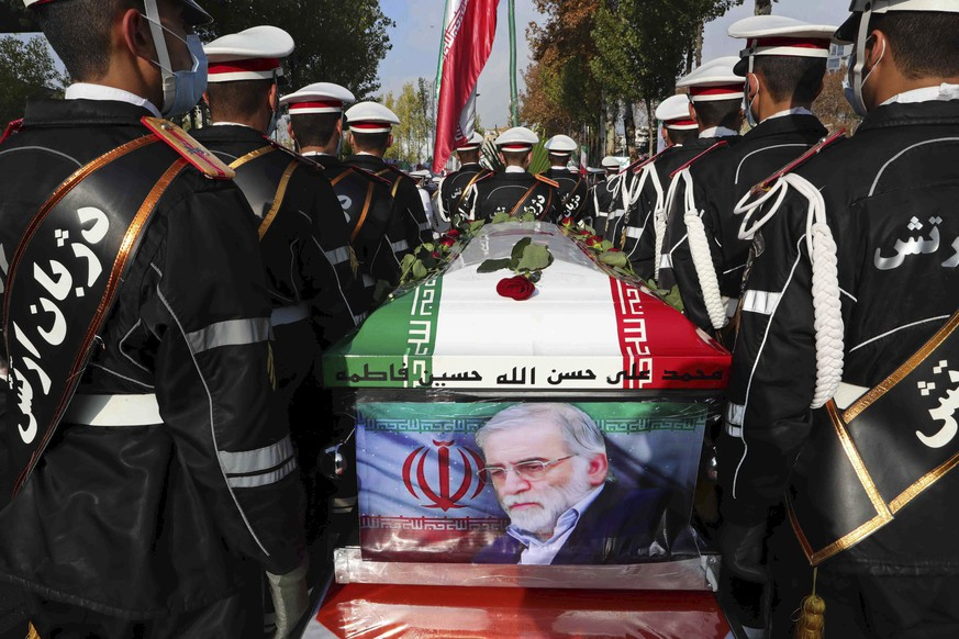 In this photo released by the official website of the Iranian Defense Ministry, military personnel stand near the flag-draped coffin of Mohsen Fakhrizadeh, a scientist who was killed on Friday, during a funeral ceremony in Tehran, Iran, Monday, Nov. 30, 2020. Fakhrizadeh founded Iran's military nuclear program two decades ago, and the Islamic Republic's defense minister vowed to continue the man's work