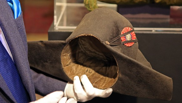 Napoleon expert Jean Claude Dey presents Napoleon's hat, from the Napoleonic collection of the Palais de Monaco, in Fontainebleau, south of Paris, France, Wednesday Nov. 12, 2014. The hat is part of the Napoleonic collection gathered by Prince Louis II, that will be put on sale Nov. 15 and Nov. 16 in Fontainbleau. More than 1,000 objects among which is Napoleon's hat, will be put on sale at this auction. Napoleon bicorn hat is on display next to the chateau where the general lived when he wasn't leading troops into battle across Europe.  The felt is a little weathered by age and use, though no one's worn it since Napoleon's veterinarian, who received from the French leader as a gift, but auctioneers are hoping to fetch 500,000 euros ($623,000) for it at the weekend auction. (AP Photo/Remy de la Mauviniere)