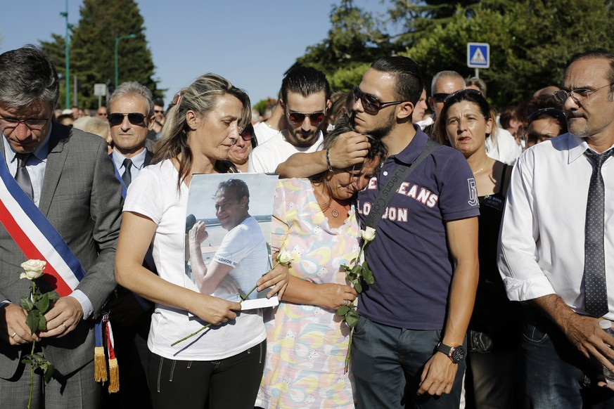 Laurence and Kevin, center, wife and son of Herve Cornara, react during a quiet march in Fontaine-sur-Saone, near Lyon, central France, Tuesday, June 30, 2015, to pay their respects to Herve Cornara, the man killed and beheaded on June 26, 2015, in a terrorist attack at the Air Products factory in Saint-Quentin-Fallavier. An attacker with suspected ties to French Islamic radicals rammed a car into a gas factory Friday in southeastern France, and a severed head was staked on a post at the entrance.  (AP Photo/Laurent Cipriani)