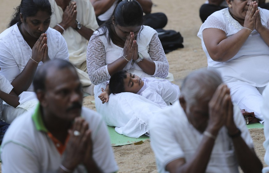 Sri Lankan Buddhists pray along with monks during a ceremony to invoke blessings on the dead and wounded from Sunday's bombings at the Kelaniya temple in Colombo, Sri Lanka, Wednesday, April 24, 2019. Sri Lanka's president has asked for the resignations of the defense secretary and national police chief, a dramatic internal shake-up after security forces shrugged off intelligence reports warning of possible attacks before Easter bombings that killed over 350 people, the president's office said Wednesday. (AP Photo/Manish Swarup)