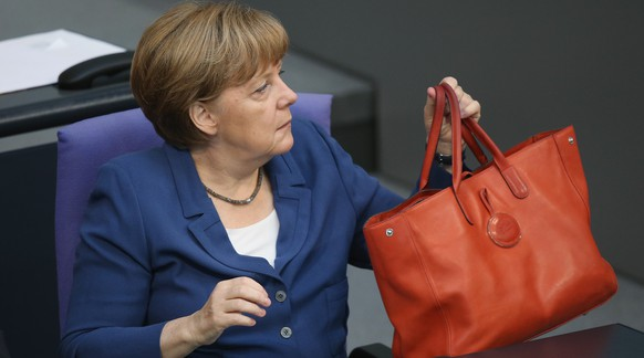 BERLIN, GERMANY - JULY 03:  German Chancellor Angela Merkel holds her handbag while she attends a session of the Bundestag on July 3, 2015 in Berlin, Germany. The Bundestag wrestled with the Greek debt crisis earlier in the week and Merkel is refusing to conduct further negotations with the Greek government until after the Greek referendum scheduled for this coming Sunday. The referendum gives the Greek population the opportunity to vote for or against acceptance of reforms demanded by the troika of the European Central Bank, the International Monetary Fund and the European Commission.  (Photo by Sean Gallup/Getty Images)
