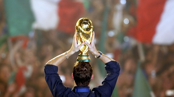 Italian national soccer team player Francesco Totti holds the World Cup on his head as he celebrates on a stage at Circus Maximus, in Rome, Monday, July 10, 2006. Italy won 5-3 over France in a penalty shootout during the final of the World Cup Germany 2006 in Berlin on Sunday. (AP Photo/Alessandra Tarantino)