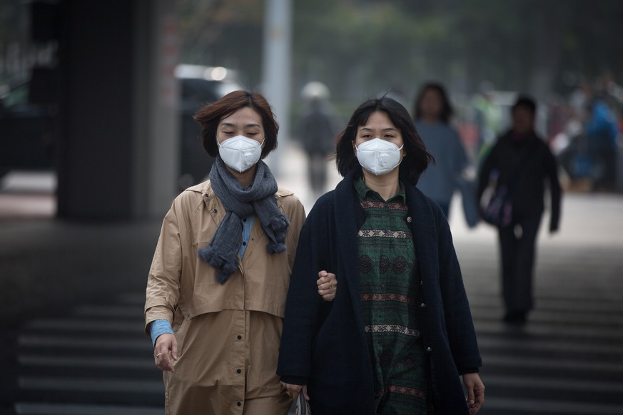 epa06292072 Chinese women wearing protective masks walk on the street in Beijing, China, 27 October 2017. Authorities in Beijing and Tianjin issued a yellow alert for pollution from 26 October. The PM 2.5 air quality index measuring fine particle air pollution in Beijing reached over 235 on 27 October.  EPA/ROMAN PILIPEY