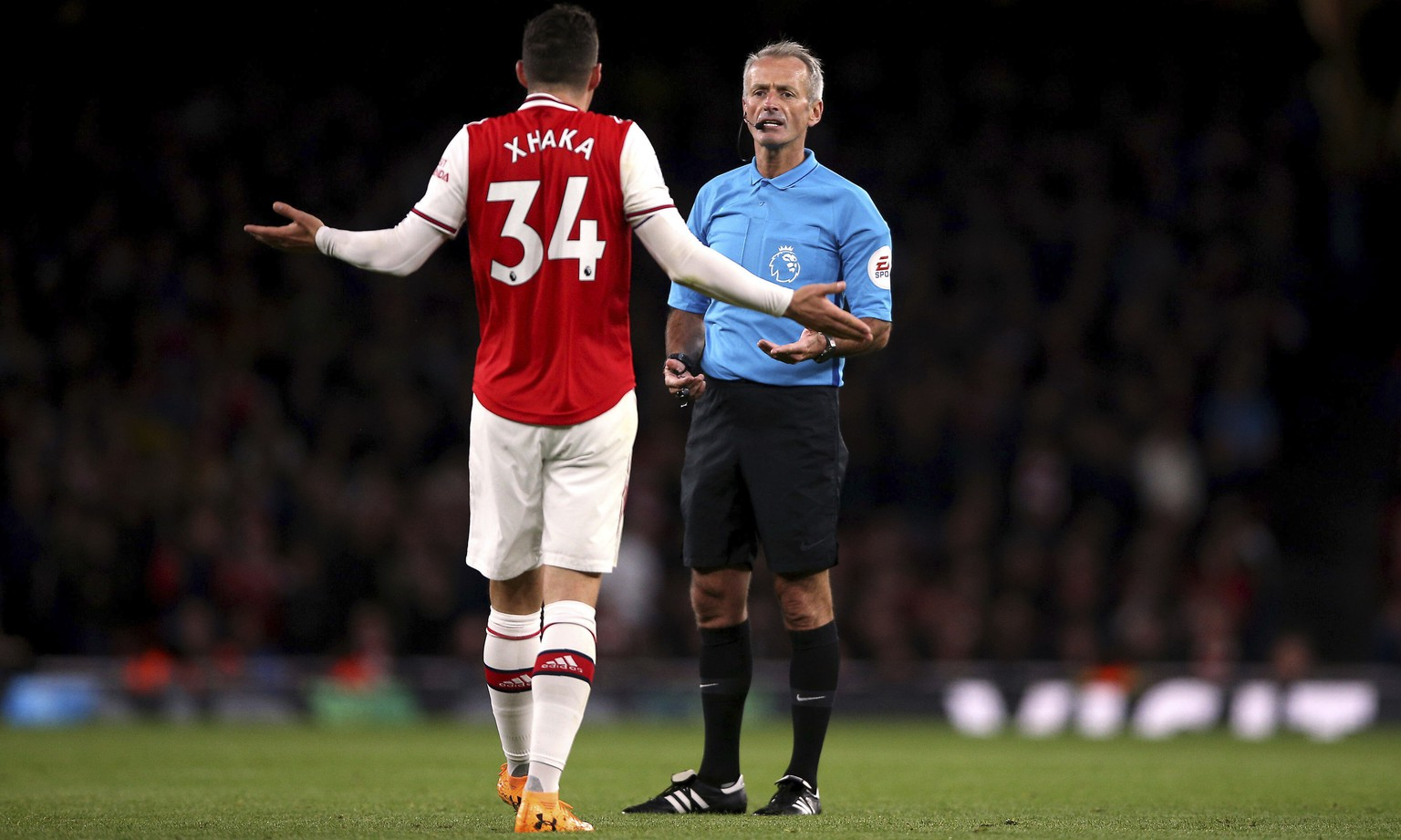 Arsenal's Granit Xhaka speaks to referee Martin Atkinson during the English Premier League soccer match at the Emirates Stadium, London, Sunday Oct. 27, 2019. (Nigel French/PA via AP)